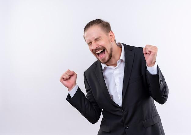 흰색 배경 위에 서 그의 성공을 기뻐하는 양복 미친 행복 떨림 주먹을 입고 잘 생긴 비즈니스 남자