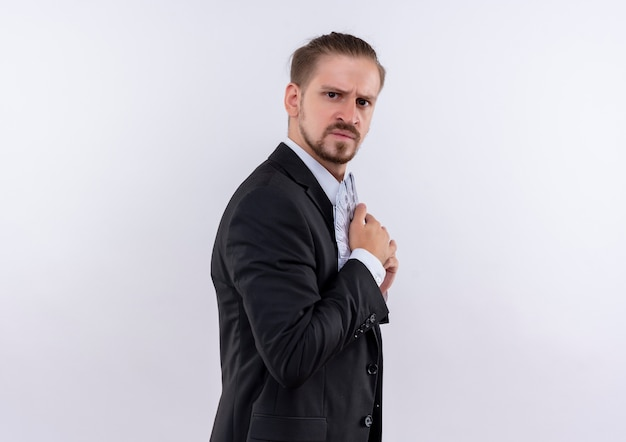 Handsome business man wearing suit hiding money in his suit with serious face standing over white background