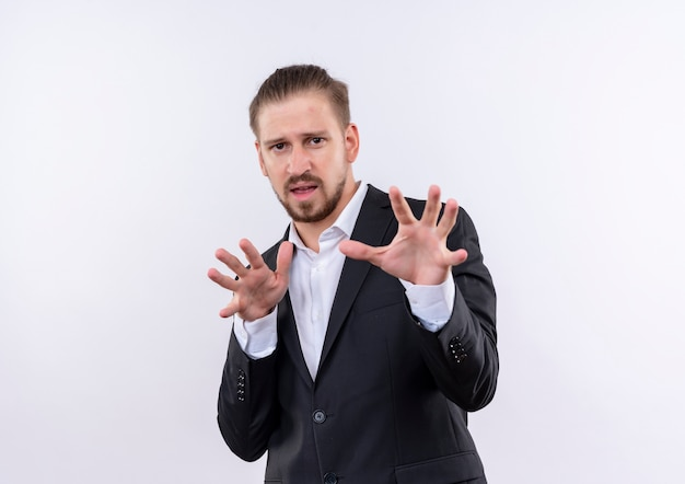 Handsome business man wearing suit holding arms out with disgusted expression standing over white background