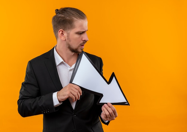 분홍색 배경 위에 서있는 화살표 기호를 들고 양복을 입고 잘 생긴 비즈니스 남자