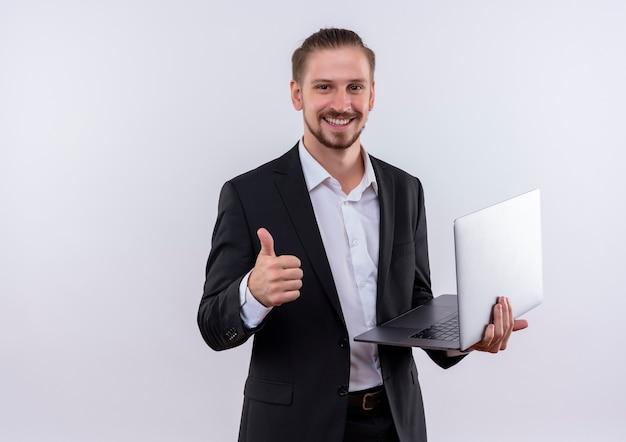 카메라를보고 빈 페이지를 들고 양복을 입고 잘 생긴 비즈니스 남자 흰색 배경 위에 서있는 엄지 손가락을 유쾌하게 보여주는 미소