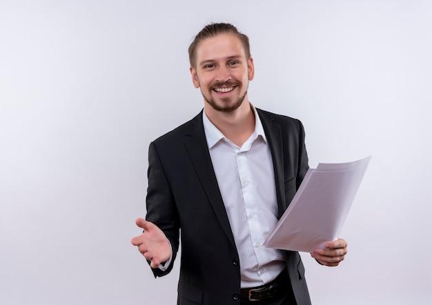 白い背景の上に元気に立って笑顔のカメラを見て空白のページを保持しているスーツを着ているハンサムなビジネスマン