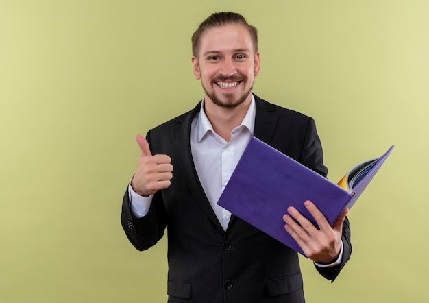 緑の背景の上に立って親指を示す笑顔でカメラを見て青いフォルダーを保持しているスーツを着ているハンサムなビジネスマン