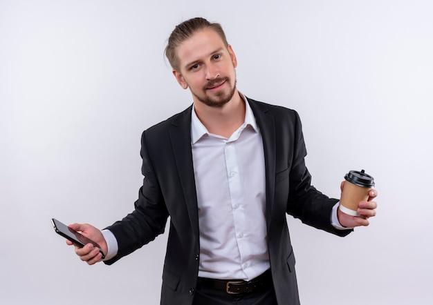 白い背景の上に立っている顔に笑顔でカメラを見てコーヒーカップとスマートフォンを保持しているスーツを着てハンサムなビジネス男