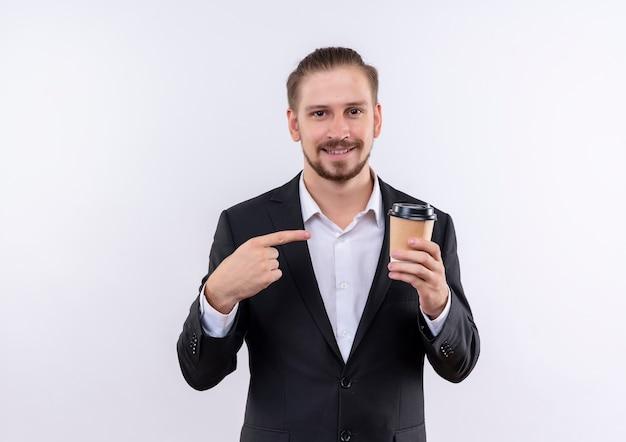 손가락으로 가리키는 커피 컵을 들고 양복을 입고 잘 생긴 비즈니스 남자는 흰색 배경 위에 서 웃고