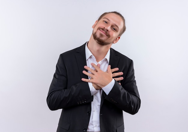 흰색 배경 위에 서있는 긍정적 인 감정을 느끼는 가슴에 손을 잡고 양복을 입고 잘 생긴 비즈니스 남자