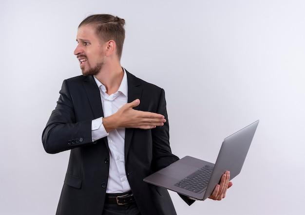 Bel uomo d'affari che indossa tuta tenendo il computer portatile alla ricerca da parte confuso e molto ansioso in piedi su sfondo bianco