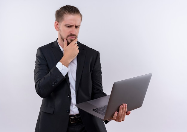 白い背景の上に立って物思いにふける表現思考でそれを見てラップトップコンピューターを保持しているスーツを着ているハンサムなビジネスマン