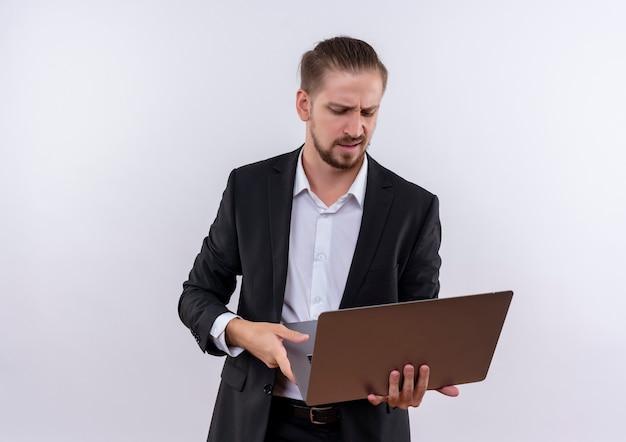 화면을보고 노트북 컴퓨터를 들고 양복을 입고 잘 생긴 비즈니스 남자는 흰색 배경 위에 서 불쾌