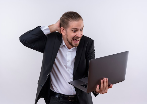 Handsome business man wearing suit holding laptop computer looking surprised and amazed standing over white background