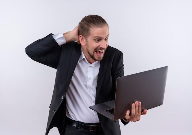 노트북 컴퓨터를 들고 양복을 입고 잘 생긴 비즈니스 남자는 흰색 배경 위에 서 놀란 놀라게 찾고