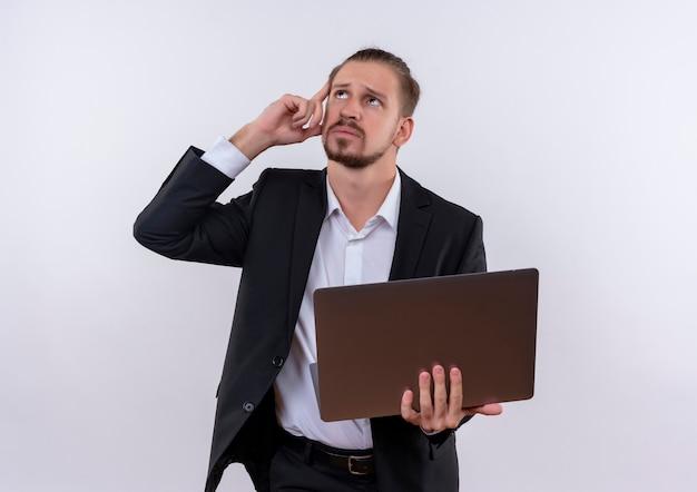 Красивый деловой человек в костюме, держащий портативный компьютер, озадаченный стоя на белом фоне