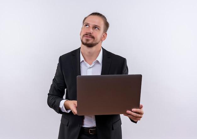 白い背景の上に立っている物思いにふける表情で見上げるラップトップコンピューターを保持しているスーツを着てハンサムなビジネス男