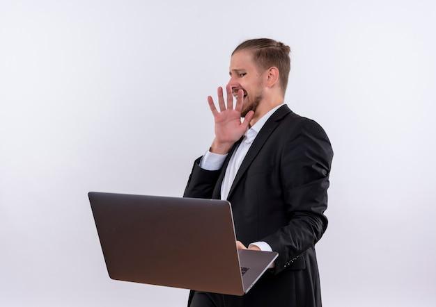 흰색 배경 위에 서 혐오 식으로 방어 제스처를 만드는 노트북 컴퓨터를 들고 양복을 입고 잘 생긴 비즈니스 남자