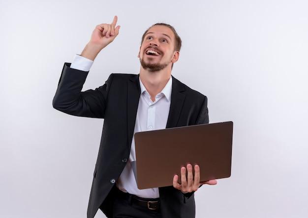 Красивый деловой человек в костюме, держащий портативный компьютер, указывая вверх пальцем, весело улыбаясь, стоя на белом фоне