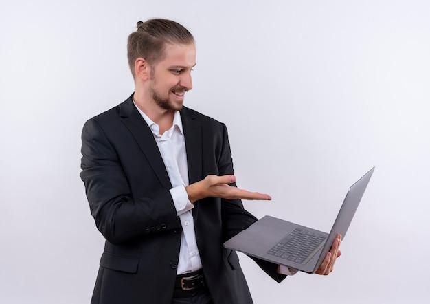 흰색 배경 위에 서있는 얼굴에 wioth 미소를 화면에 팔으로 가리키는 노트북 컴퓨터를 들고 양복을 입고 잘 생긴 비즈니스 남자