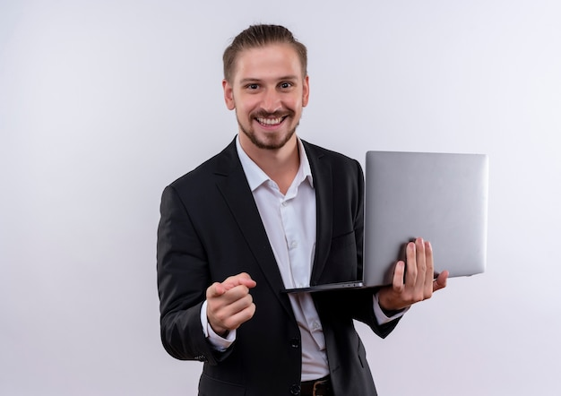 Handsome business man wearing suit holding laptop computer pointing with finger to camera smiling cheerfully standing over white background