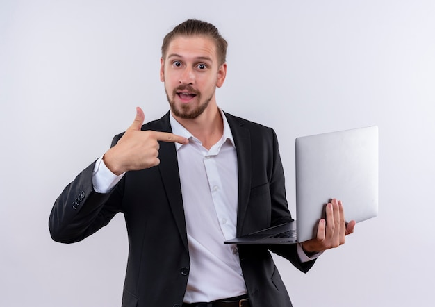 Handsome business man wearing suit holding laptop computer pointing with finger to it smiling cheerfully standing over white background