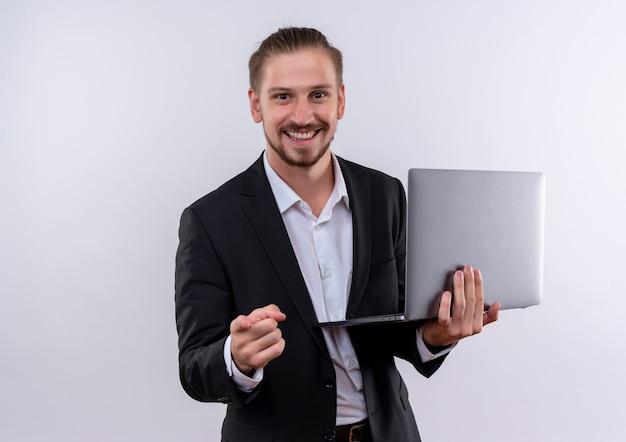 Красивый деловой человек в костюме, держащий портативный компьютер, указывая пальцем на камеру, весело улыбаясь, стоя на белом фоне