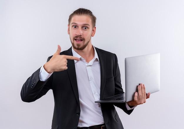 Красивый деловой человек в костюме, держащий портативный компьютер, указывая пальцем на него, весело улыбаясь, стоя на белом фоне