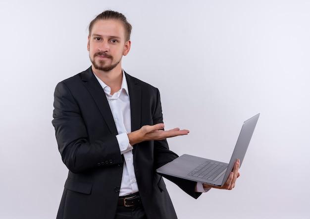 Bel uomo d'affari che indossa tuta tenendo il computer portatile che presenta con il braccio della mano cercando fiducioso in piedi su sfondo bianco