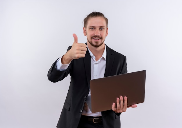 노트북 컴퓨터를 들고 양복을 입고 잘 생긴 비즈니스 남자는 흰색 배경 위에 서있는 카메라를보고 엄지 손가락을 유쾌하게 보여주는 미소