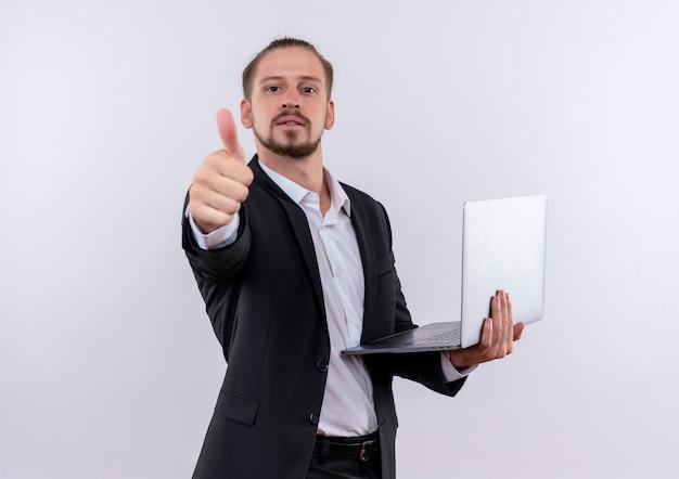 노트북 컴퓨터를 들고 양복을 입고 잘 생긴 비즈니스 남자는 흰색 배경 위에 서 엄지 손가락을 유쾌하게 보여주는 미소