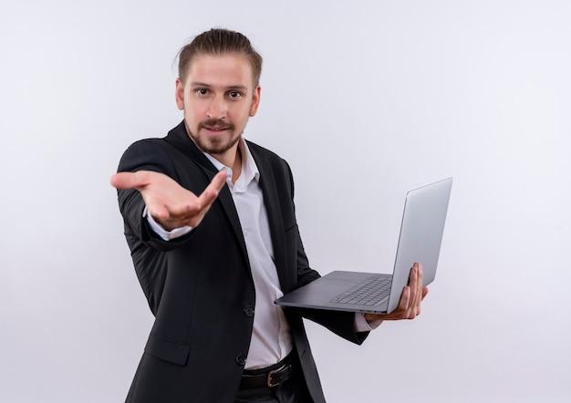 白い背景の上に立っている顔に笑顔でカメラを見て腕を持ってラップトップコンピューターを保持しているスーツを着てハンサムなビジネス男