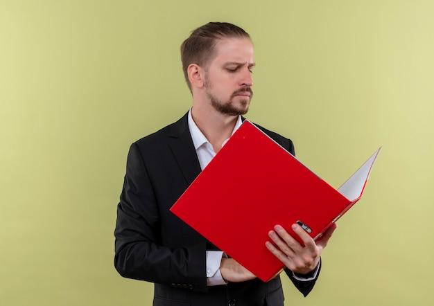 緑の背景の上に立っている深刻な顔でそれを見て赤いフォルダーを保持しているスーツを着ているハンサムなビジネスマン