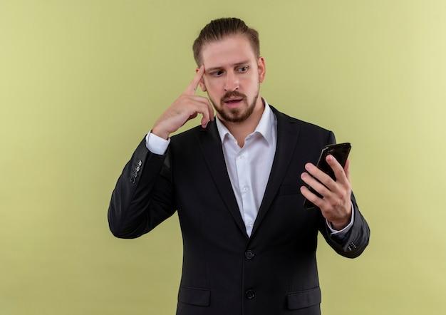 Красивый деловой человек в костюме, держащий смартфон, глядя на экран, смущенный стоя на зеленом фоне