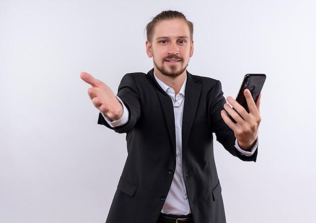 白い背景の上に立っているカメラを見てフレンドリーな笑顔の手で歓迎のジェスチャーを作るスマートフォンを保持しているスーツを着ているハンサムなビジネスマン