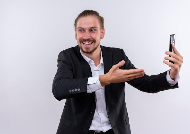 Bel uomo d'affari che indossa tuta tenendo lo smartphone presentandolo con il braccio della sua mano sorridendo allegramente in piedi su sfondo bianco