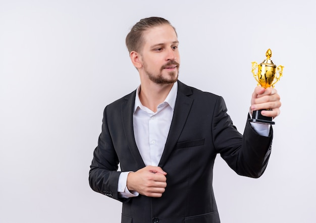 Handsome business man wearing suit holding trophy looking at it with smile on face standing over white background