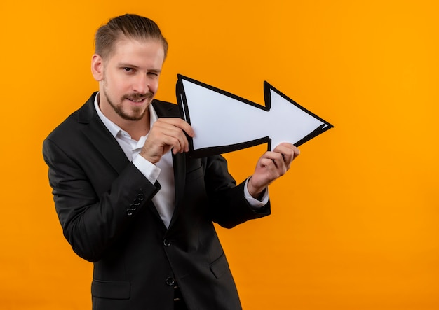 Handsome business man wearing suit holding white arrow looking at camera smiling and winking standing over orange background