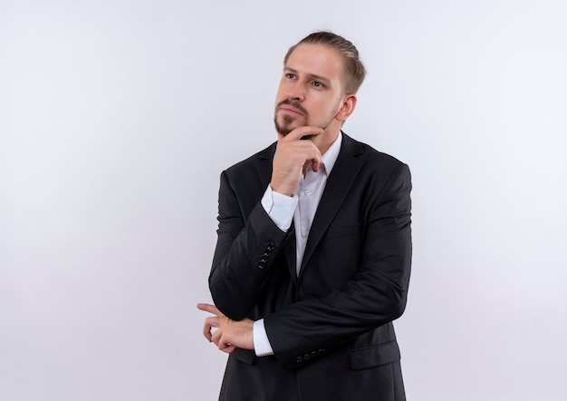 Bel uomo d'affari che indossa tuta guardando da parte con la mano sul mento con espressione pensierosa in piedi su sfondo bianco