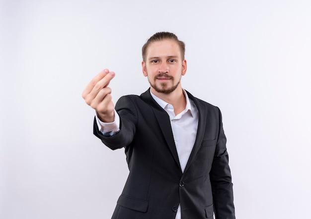白い背景の上に立ってお金のジェスチャーを作るカメラをこする指を見てスーツを着ているハンサムなビジネスマン