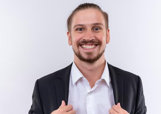 白い背景の上に立っている幸せな顔で広く笑顔のカメラを見てスーツを着てハンサムなビジネス男