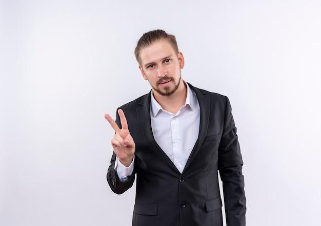 白い背景の上に立っている勝利のサインを示す自信を持って笑顔のカメラを見てスーツを着てハンサムなビジネス男
