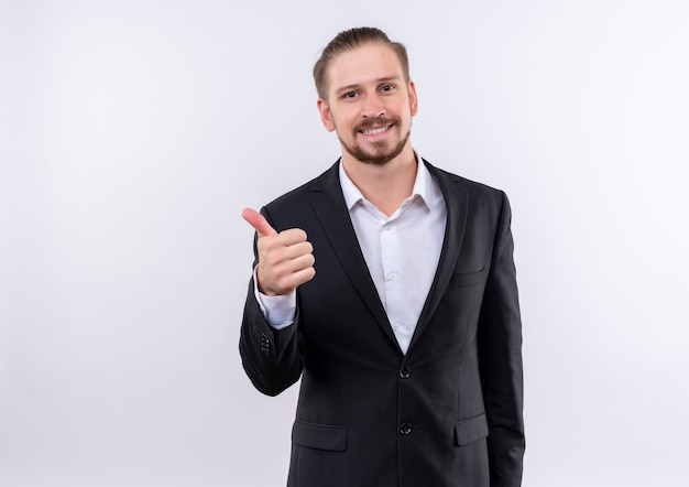 흰색 배경 위에 서 엄지 손가락을 보여주는 미소를 카메라를보고 양복을 입고 잘 생긴 비즈니스 남자