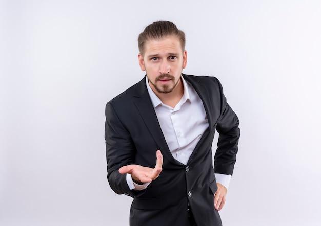 Красивый деловой человек в костюме смотрит в камеру с вытянутой рукой, задавая вопрос, стоя на белом фоне