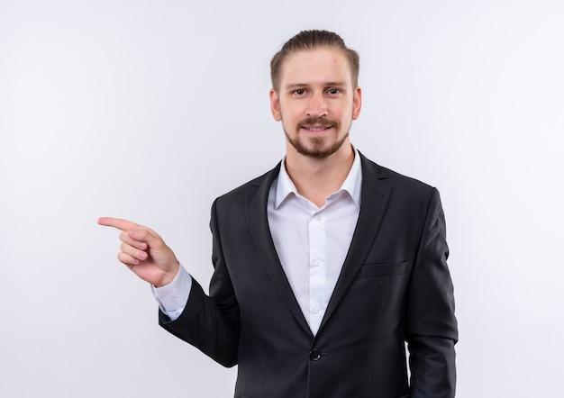 白い背景の上に立っている側に人差し指で指している自信を持って笑顔でカメラを見てスーツを着ているハンサムなビジネスマン
