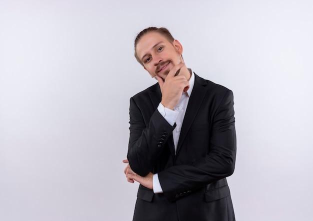 흰색 배경 위에 긍정적 인 서 생각 잠겨있는 표정으로 카메라를보고 양복을 입고 잘 생긴 비즈니스 남자