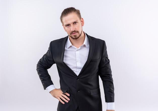 白い背景の上に立っている真剣な自信を持ってカメラを見てスーツを着ているハンサムなビジネスマン