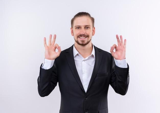 Bel uomo d'affari che indossa tuta guardando la telecamera sorridente che mostra ok cantare con entrambe le mani in piedi su sfondo bianco