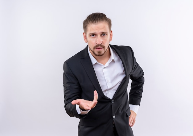 Handsome business man wearing suit looking at camera with arm out as asking question standing over white background