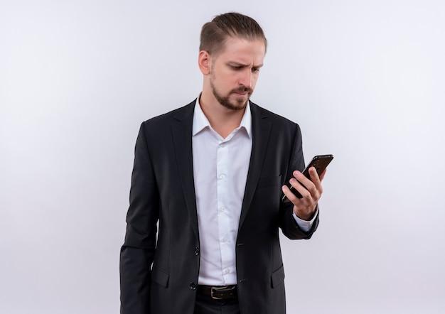 Bel uomo d'affari che indossa tuta guardando il suo smartphone confuso in piedi su sfondo bianco