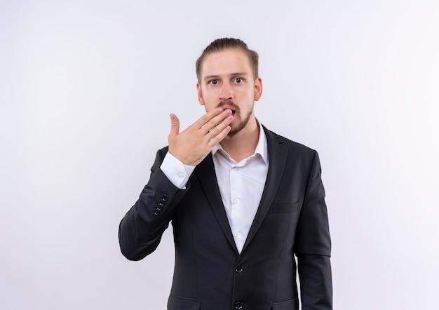 Bel uomo d'affari che indossa tuta guardando sorpreso e stupito che copre la bocca con la mano in piedi su sfondo bianco