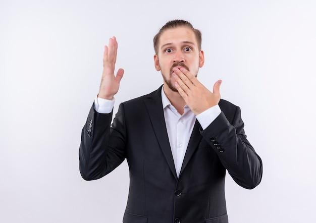 Bel uomo d'affari che indossa tuta guardando sorpreso che copre la bocca con la mano in piedi su sfondo bianco