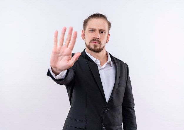 Красивый деловой человек в костюме делает знак остановки с открытой рукой, глядя в камеру с серьезным лицом, стоящим на белом фоне
