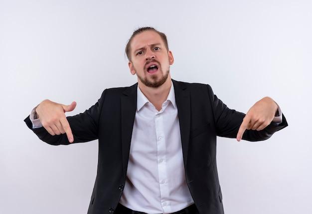 Bel uomo d'affari che indossa tuta che punta con il dito indice verso il basso con la faccia seria in piedi su sfondo bianco